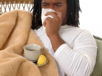 a young man with a cold covered in a blanket and drinking hot tea